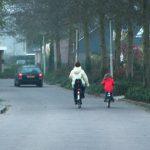 Een behoedzaam kind op de fiets met moeder