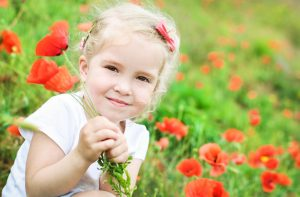 Een hoogsensitief meisje in een wei met rode klaprozen